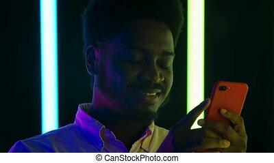 texting, smartphone., portrait, haut., africaine, sourire, jeune, lent, fin, élégant, sien, motion., mâle, américain