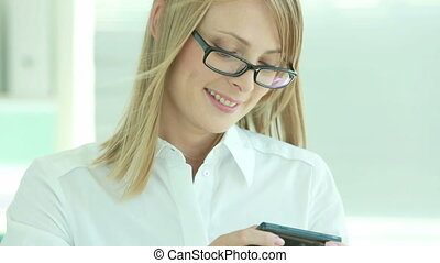 Texting - Smiling business girl reading a funny message and...