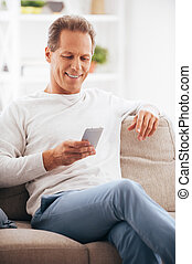 Texting to friend. Confident mature man holding mobile phone and looking at it with smile while sitting on the couch at home