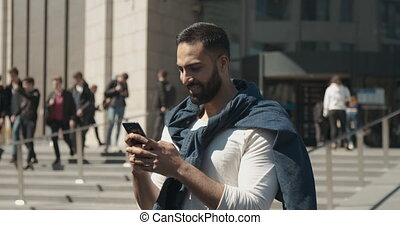 Texting with Smartphone - Handsome smiling eastern bearded...