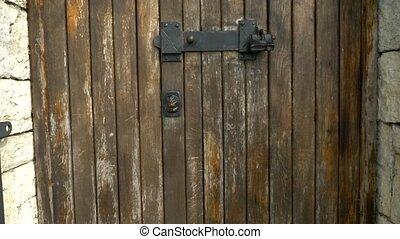 textural background, old door of wooden planks with vintage broken door handle in the form of a lion's head