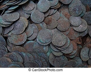texture of a pile of old silver coins in the ground