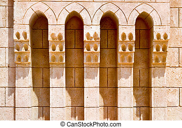 Texture of brown old ancient beautiful brick carved textured Arab Islamic Islamic wall with ornament and arches. The background.