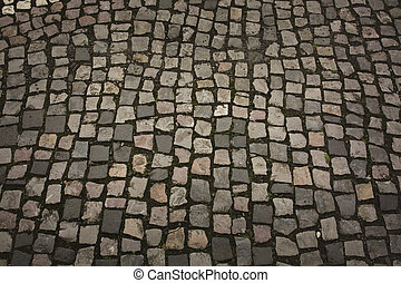Texture of cobbles with grass in the city center