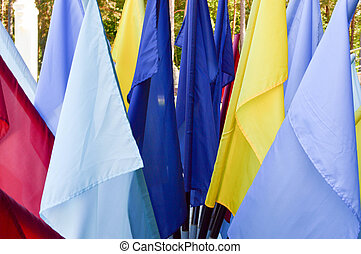 Texture of multi-colored festive red, blue, yellow flags made of fabric. The background