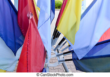 Texture of multi-colored festive red, blue, yellow flags made of fabric. The background.