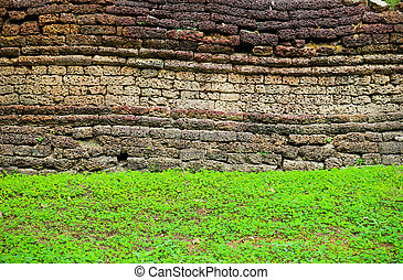 Texture of rough brick wall with grass