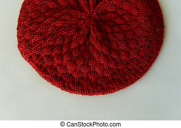 Texture red knitted beret made of wool.