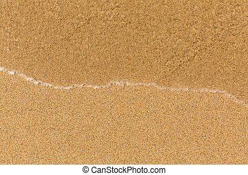 Texture sand beach with soft waves.