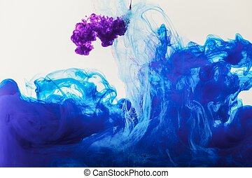 texture with flowing blue and purple paint in water, isolated on white