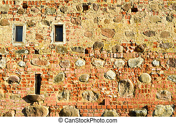 Texture with small narrow windows on an old ancient stone cracked dilapidated brick wall of red brick with large boulders. The background