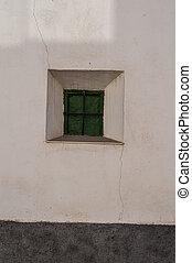 textured white wall with small window