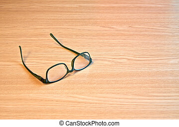 Textured wooden table and eyeglasses in close up
