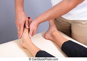 thérapeute, masage, femme, main, donner, pied