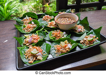"""Thai appetizer called """"Miang Kham"""" in tray on wooden table"""