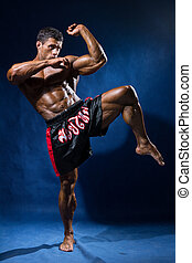 Thai boxer in full growth in a rack on a blue background.
