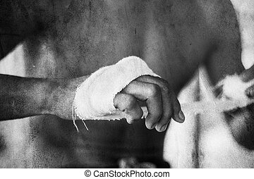 Thai boxer prepares for training by wrapping his hand with calico