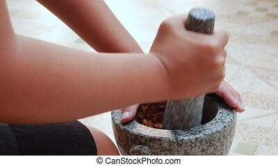 Thai chilli and garlic pounding in stone mortar with pestle....