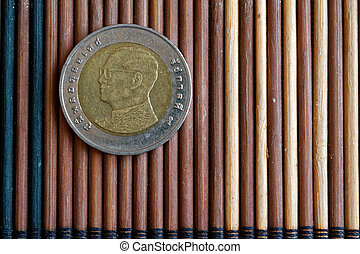 Thai coin denomination is 10 baht lie on wooden bamboo table, good for background or postcard - back side
