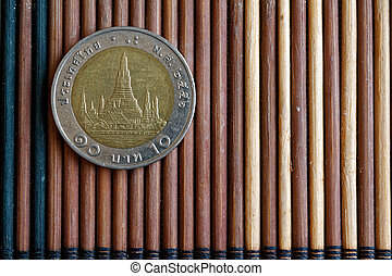 Thai coin denomination is 10 baht lie on wooden bamboo table, good for background or postcard