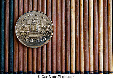 Thai coin denomination is 5 baht lie on wooden bamboo table, good for background or postcard