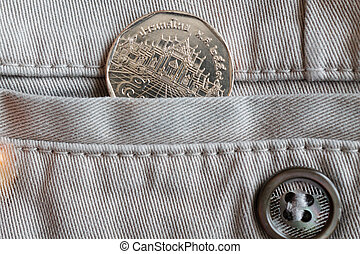 Thai coin with a denomination of 5 baht in the pocket of beige denim jeans with button