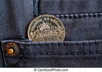 Thai coin with a denomination of 5 baht in the pocket of gray denim jeans