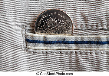 Thai coin with a denomination of five baht in the pocket of beige denim jeans with blue stripe