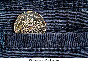 Thai coin with a denomination of five baht in the pocket of dark blue denim jeans