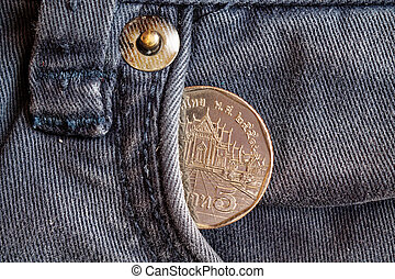 Thai coin with a denomination of five baht in the pocket of obsolete blue denim jeans