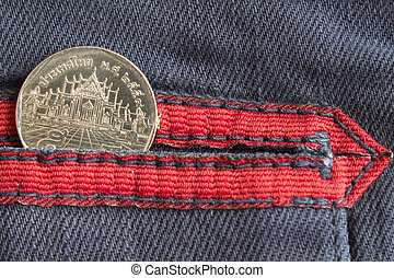 Thai coin with a denomination of five baht in the pocket of worn blue denim jeans with red stripe