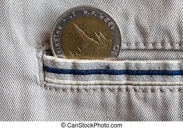 Thai coin with a denomination of ten baht in the pocket of beige denim jeans with blue stripe