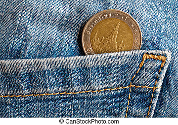 Thai coin with a denomination of ten baht in the pocket of old blue worn denim jeans