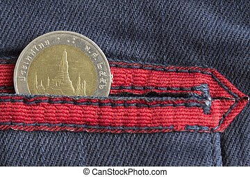 Thai coin with a denomination of ten baht in the pocket of worn blue denim jeans with red stripe