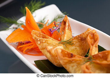 Fried thai crab cream cheese wontons or rangoons appetizer presented on a platter with fancy carrot and herb garnish.