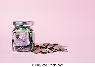 Thai currency banknote and coins in the glass jar on pink background for business, finance, investment and saving money concept