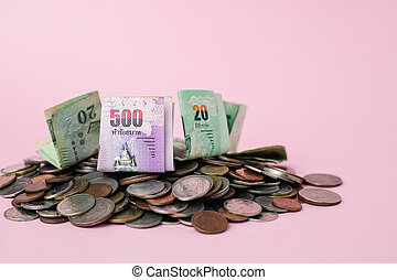 Thai currency banknote and money coins on pink background for business, finance, investment and saving money concept