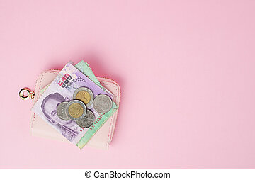 Thai currency banknote and money coins with wallet on pink background for business, finance, investment and saving money concept