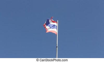Thai flag of Thailand waving by windy blue sky