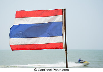Thai flag on the beach with jetski in background