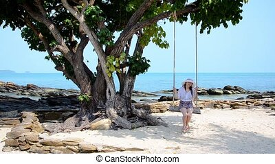 thai beach, girl on a swing in a windy day