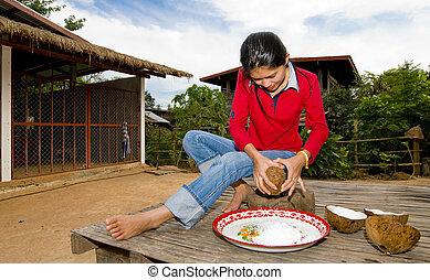 thai girl removing coconut meat from shell - thai girl...