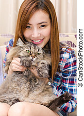 Thai girl with a cat. - Young cute woman holding her pet...