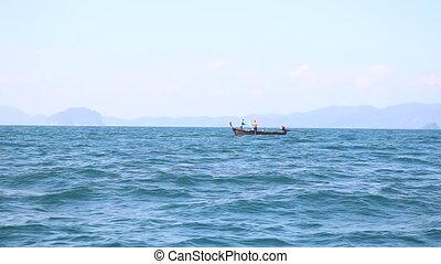 thai longtail boat in sea against islands