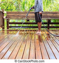 Thai man do a pressure washing on timber