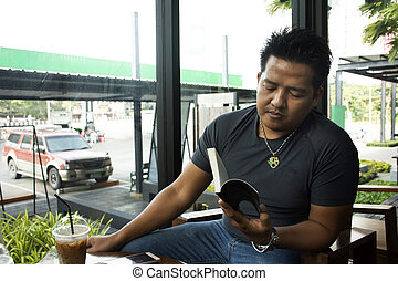Thai man sitting relaxed reading book and talking with drinking ice coffee in cafe shop