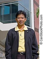 Thai man standing outside a university building