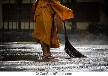 thai monk daily cleaning in buddist temple