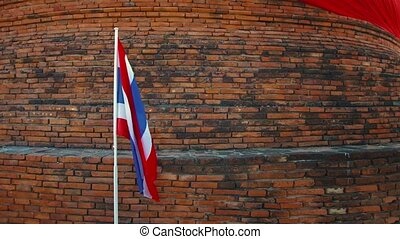 Video 4k - The alternating red, white and blue striped, Thai national flag, fluttering gently in the breeze from its wall-mounted pole in Ayutthaya, Thailand