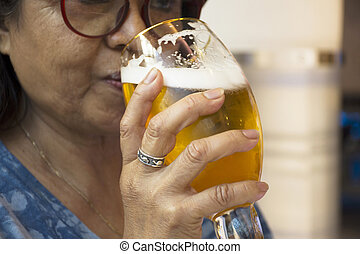 Thai old woman drinking beer czech style in glass